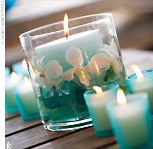 short vases with candles and orchids submerged in turquoise water. Rows of flickering turquoise votives completed the look.
