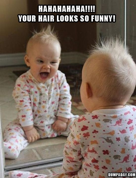 funny baby looks in the mirror