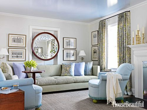 "After his client downsized to a smaller house in Summit, New Jersey, designer Kevin Isbell accommodated her 12-foot-long sofa in the living room by putting it against a wall with a doorway. To ""defuse the fact,"" he hung her showstopping 19th-century sorcerer's mirror above it, creating the feeling of a solid wall."