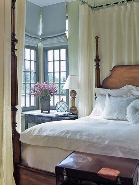 The marsh-green guest bedroom dons a misty blue ceiling and provides relaxing accommodations. A custom-made linen bed tent swathes the honey-finished four-poster bed. (Photo: Photo: Jean Allsopp;)