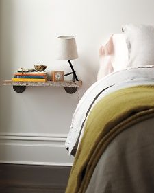 Save floor space by replacing your nightstand with a bracketed shelf.