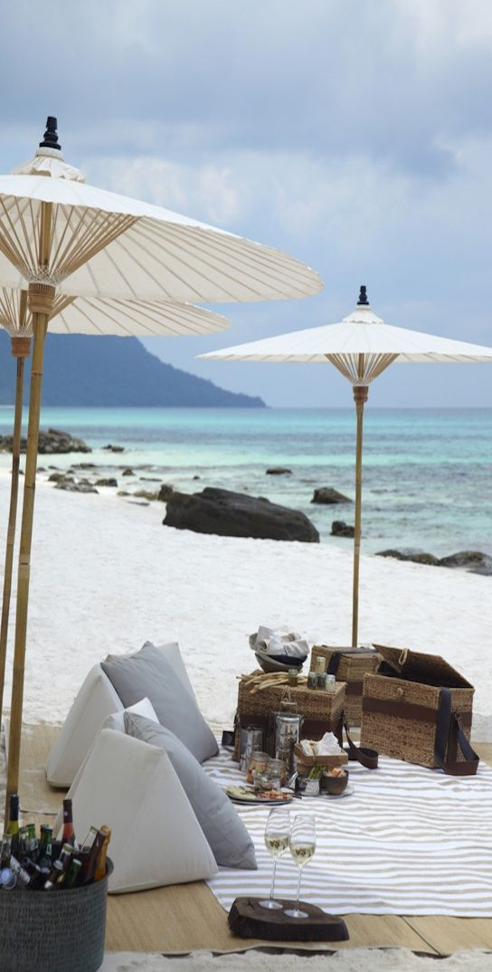 Create a #chic spot for #entertaining on the beach with cool cushions, #parasols and #vintage baskets for provisions.