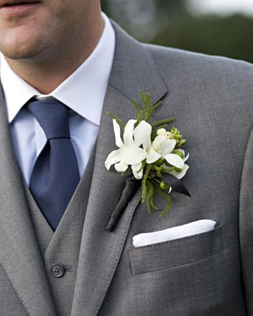 grey tux, grey vest, and navy blue tie & coral flowers