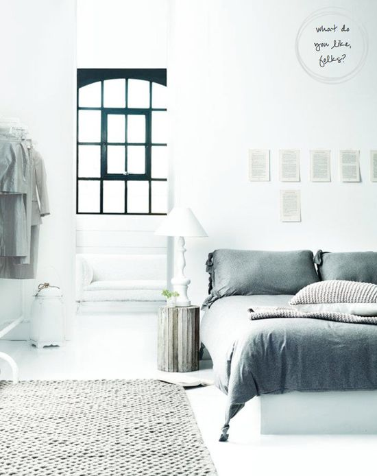 Soft and relaxed bedroom: the white, the gray, the pages on the wall and black trimmed window