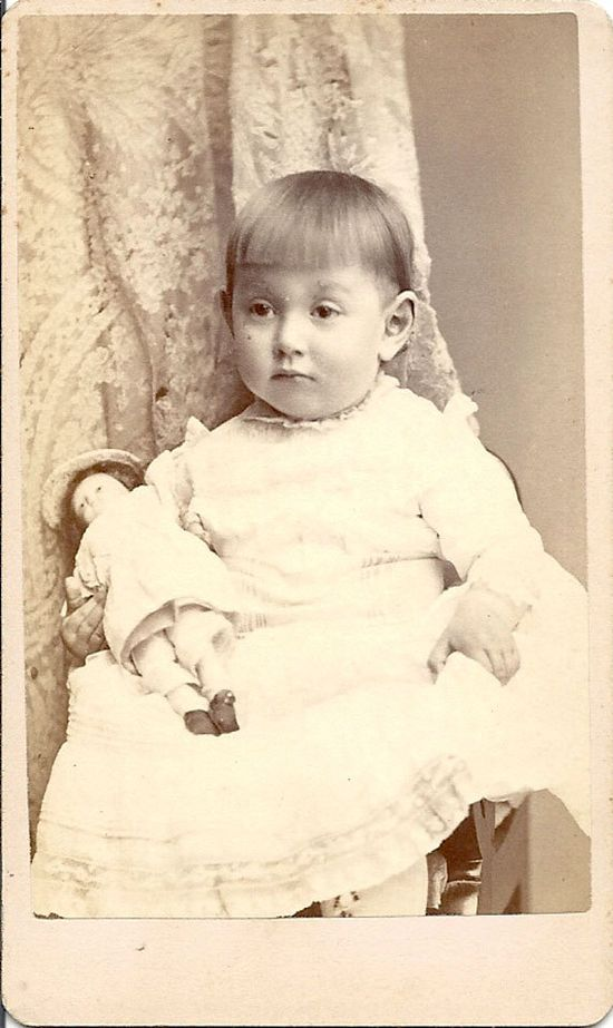 Great CDV of a little girl with freshly cut bangs holding her doll. Circa 1890 - 1900.