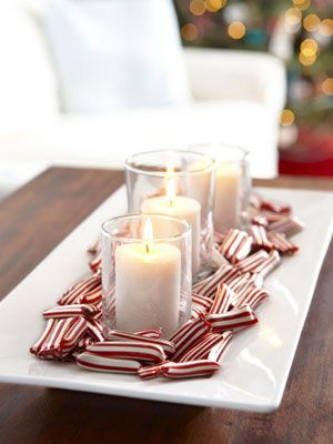 Candy cane candy bites surround votives on white tray.
