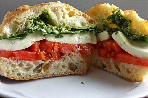 Caprese sandwich with tomato, pesto, and fresh mozzarella.