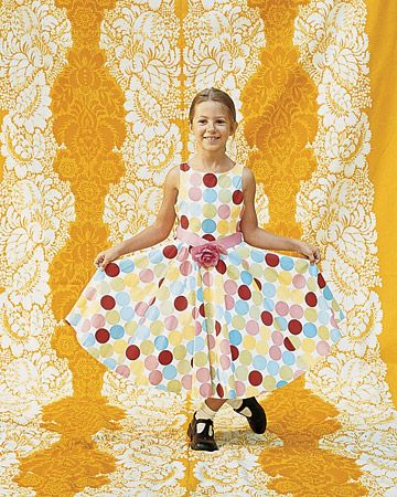 This flower girl's spotty dress stands out against the bold yellow backdrop