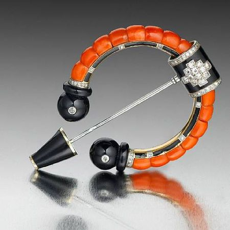 A fine art deco onyx, coral, enamel, and diamond brooch by Cartier, circa 1925.