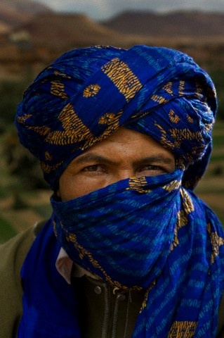 A young man sits on the roadside with his face masked by a blue scarf wrapped around his head and face in central Morocco.