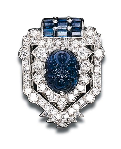 AN ART DECO SAPPHIRE AND DIAMOND CLIP BROOCH, BY CARTIER   Designed as a circular-cut diamond stylised shield-shaped panel set with a central carved cabochon sapphire to the calibré-cut sapphire terminal, circa 1925  Signed Cartier, number indistinct