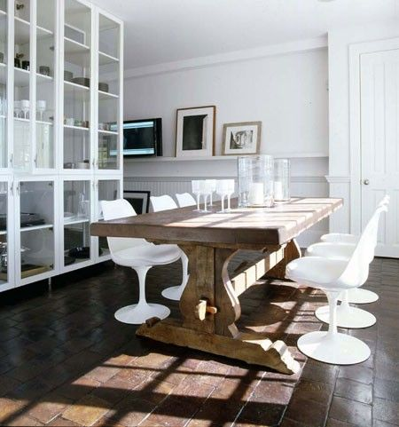 Rustic dining table with modern chairs - great combination in Vincente Wolf's dining room.