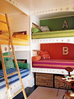 In a coastal vacation home, the children's bunkroom is decorated with a tropical color palette of sunshine yellow, cobalt, lime and tangerine. Each bunk has its own storage basket at the head of the bed and a larger storage basket below.