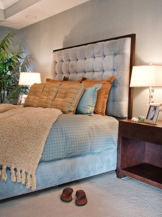 An ice-blue suede headboard complements the blue and toffee bedding. The deep tufting provides a comfy leaning surface for reading in bed.
