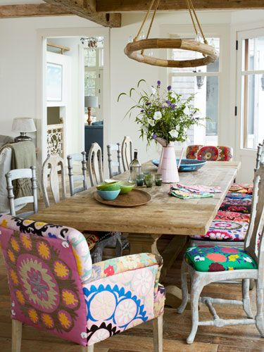 Suzani fabric covers silver-painted wood seats by Redford House and Zentiques armchairs and birch sidechairs. The pine dining table is from Restoration Hardware.