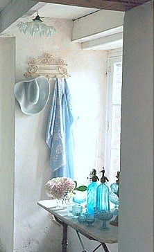 These collection of blue bottles near a window give a very fresh look to the bathroom.