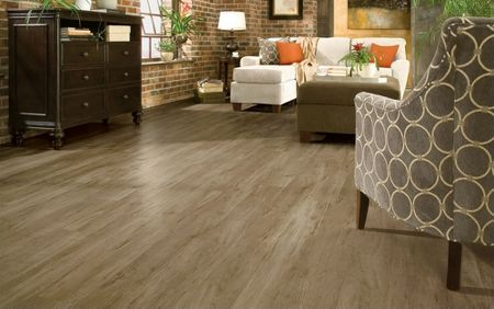 The right floor can pull a whole room together. The dark tone of this barnyard gray wood-look vinyl floor combines well with the slate, cream, and chocolate furniture. It's a dramatic, non-traditional flooring choice.  seem to melt right into the room. Your living room flooring should be the icing on the cake, not the elephant in the room.