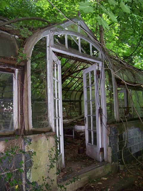Aging greenhouse with double doors.