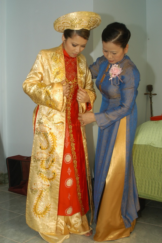 Mother helping her daughter into wedding ao dai, a life turning event for many lady as they start their family.