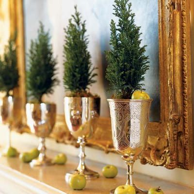 miniature trees or evergreen tips in silver goblets with green apples - charming.