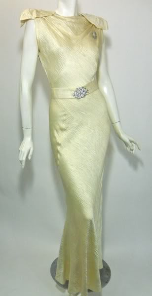 Hands down one of the most amazing 1930s gowns I've had the pleasure to offer! Ivory crepe back, texured satin silk bias cut gown has flat bows atop shirred shoulders, deco rhinestone sash and deep V back. Coordinating capelet has cowl neck in front and rhinestone buttons down back