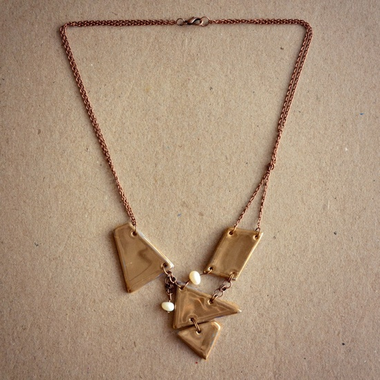 Made of gold painted ceramics, glazed and high-fired, this asymmetrical necklace will not let you pass unnoticed. $42.00.