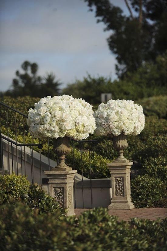 A duet of white flower arrangements.