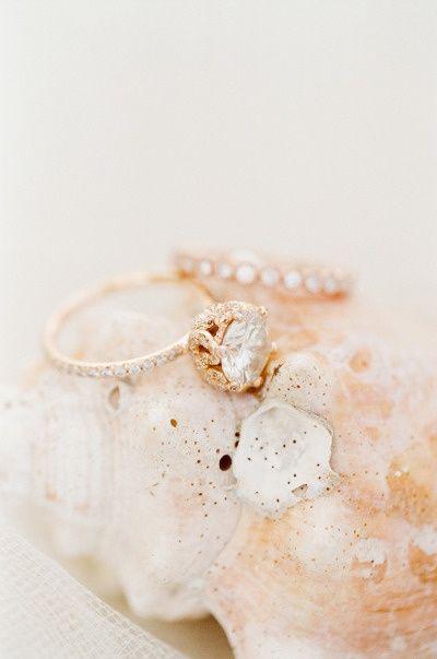 Rose gold engagement ring with tiny diamond band and raised center diamond. Matching wraparound diamond wedding band.