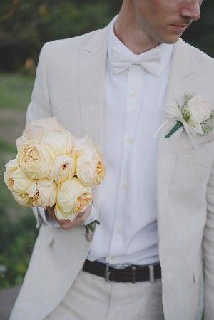 Groom holding peach garden rose bouquet