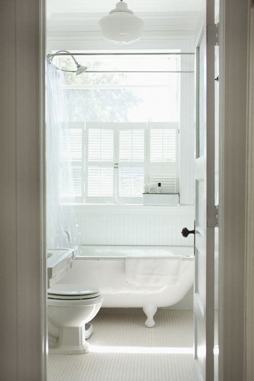 This bathroom, with its salvaged clawfoot tub, is a vision in white. See the full home tour here at Sneak Peek: Alexandra Grablewski and Todd Bonne. #sneakpeek