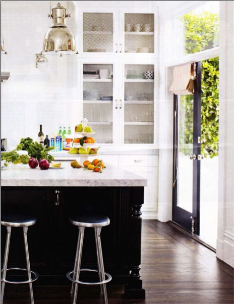 Black and white kitchen, black island, marble countertop, white glass front cabinet, white cabinet, tall cabinet, pendant, outside door, roman shade