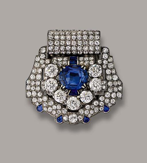 AN ART DECO SAPPHIRE AND DIAMOND CLIP BROOCH, BY CARTIER   Of shield design, the central cushion-shaped sapphire and diamond border to the pavé-set diamond surround with sapphire detail, circa 1930, 4.0 cm. wide, with French assay marks for platinum  Signed Cartier Paris, Londres, New York, No. 8605