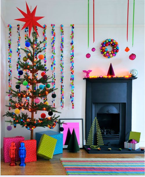 I love this room in so many ways, from the sparse little tree and bright colors to the garlands on the wall and rock-em-sock-em robots! LOVE