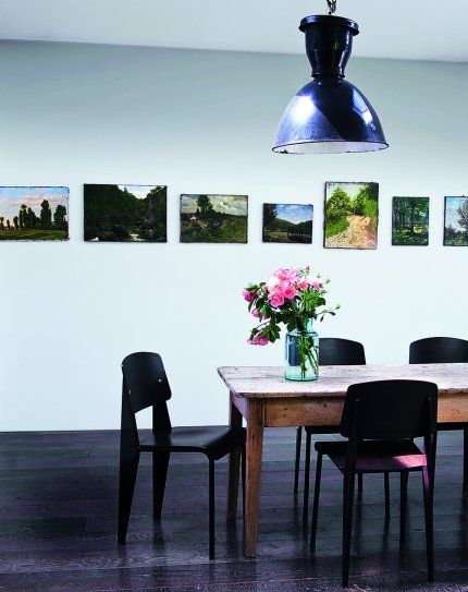 paintings with the white walls and dark furniture.