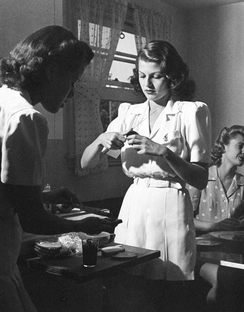 Rita Hayworth peels tomatoes while her friend, Virginia Hovey, prepares jelly sandwiches for bicycle and picnic outing in Westwood, California - June, 1940. Photographed by Peter Stackpole