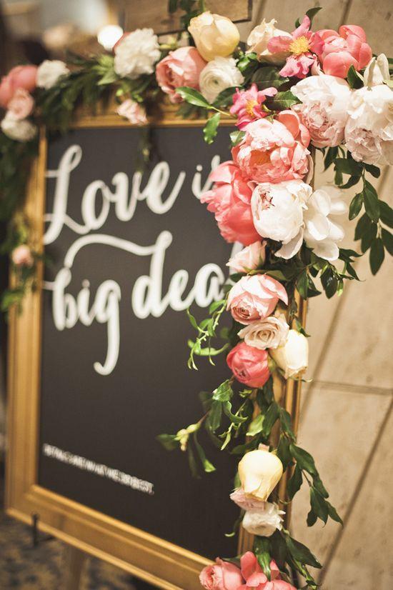 'love is a big deal' // flower adorned wedding sign