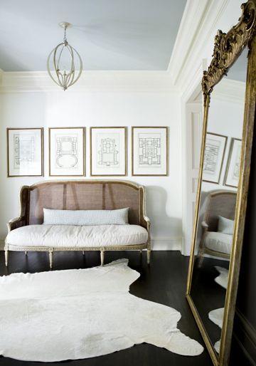 Melanie Turner. Black floor, white rug, leaning mirror, gold