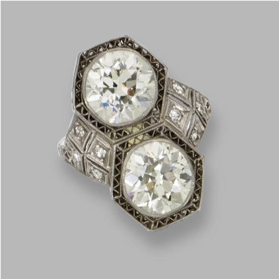 Great Art Deco style.  PLATINUM AND DIAMOND RING / C. 1925 / Old European-cut diamonds weighing approximately 2.50 and 2.40 carats, framed by small old European-cut and single-cut diamonds
