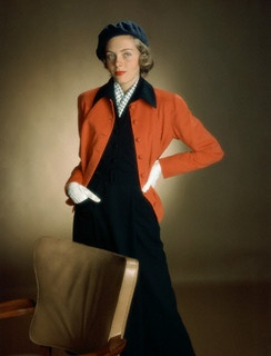 Model is wearing a deep-throated two-piece dress in navy with a straight little cardigan jacket in red, 1949. #fall #winter #vintage #fashion #1940s