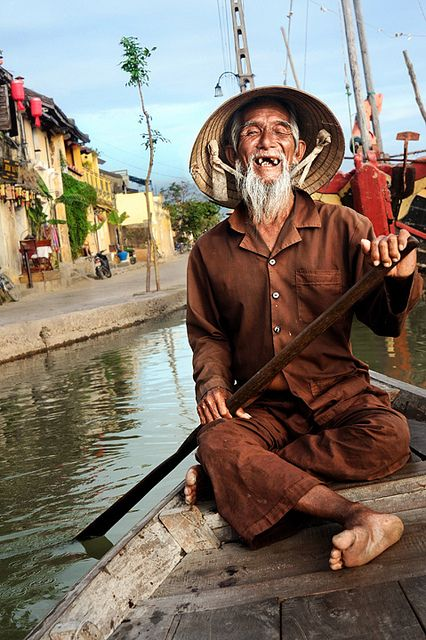 Vietnamese Boatman    An old and cheerful Vietnamese boatman paddles through the waterways of Hoi An, Vietnam.