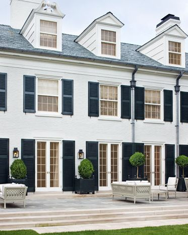 So preppy: white house, black shutters, boxwoods in black planter boxes. Just needs orange & pink French accents.