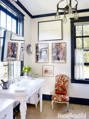 A dainty Elsie de Wolfe-style chair and a pair of surreal photographs by Jean-François Fourtou create their own kind of contrast in a master bathroom. Design: Brian McCarthy.