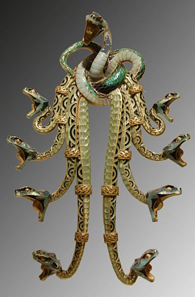 Lalique (1900). The pectoral is made up of nine serpents entwined to form a knot from which the bodies of the other eight fall in a cascade, the ninth rising in the centre, at the top of the jewel. The reptiles, in the attack position, have their mouths open from which strings of pearls were hung as was apparently the case with a similar pectoral (the whereabouts of which are unknown), which was highlighted at the Paris Universal Exhibition in 1900 and reproduced in a publication of the period.