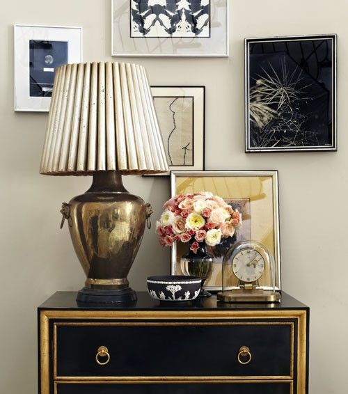 black and gold = love!  Gold lamp, black console, black and white art.