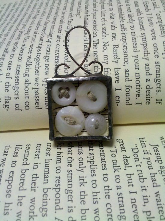 four vintage buttons in a soldered frame