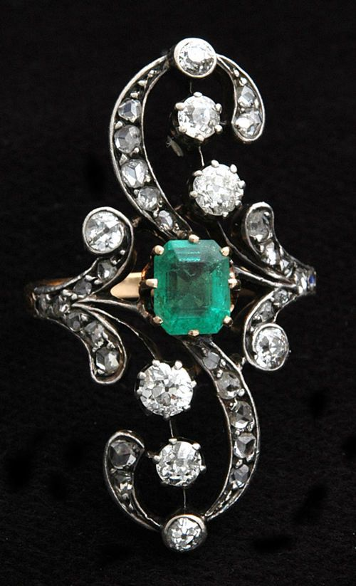 """From Russia and circa 1890, this isan emerald and diamond dress ring. The central trap-cut (also known as """"step-cut"""") emerald is set in 18k..."""