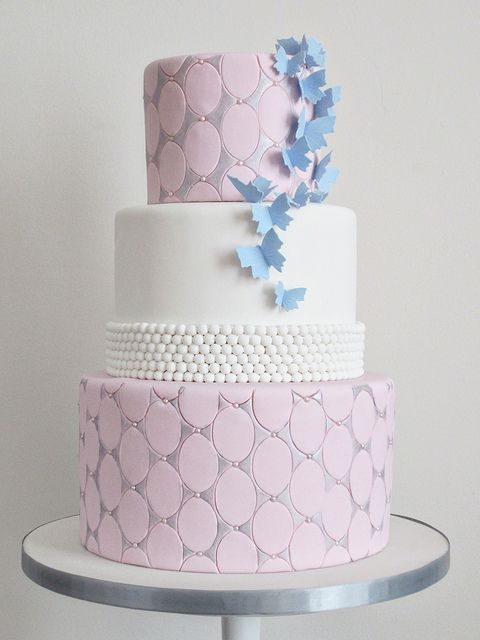 White, pink and silver couture wedding cake with pearls and blue butterflies