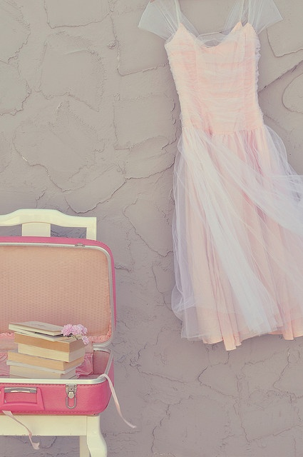 Pink dress beside a Pink vintage suitcase