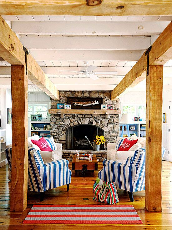 Exposed beams and a stone fireplace add rustic appeal to this cozy space. See more ideas for stylish spaces: www.bhg.com/...