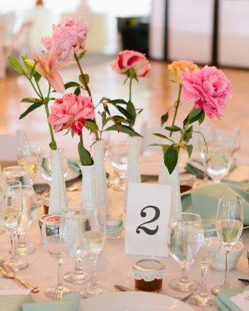 Single pink blooms in white vases are simple and elegant